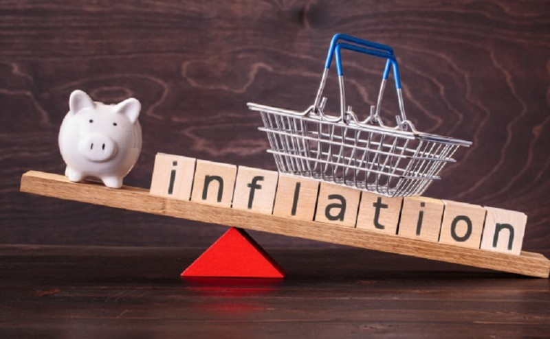 Inflation spelled in letters with shopping basket and piggy bank on seesaw against dark background